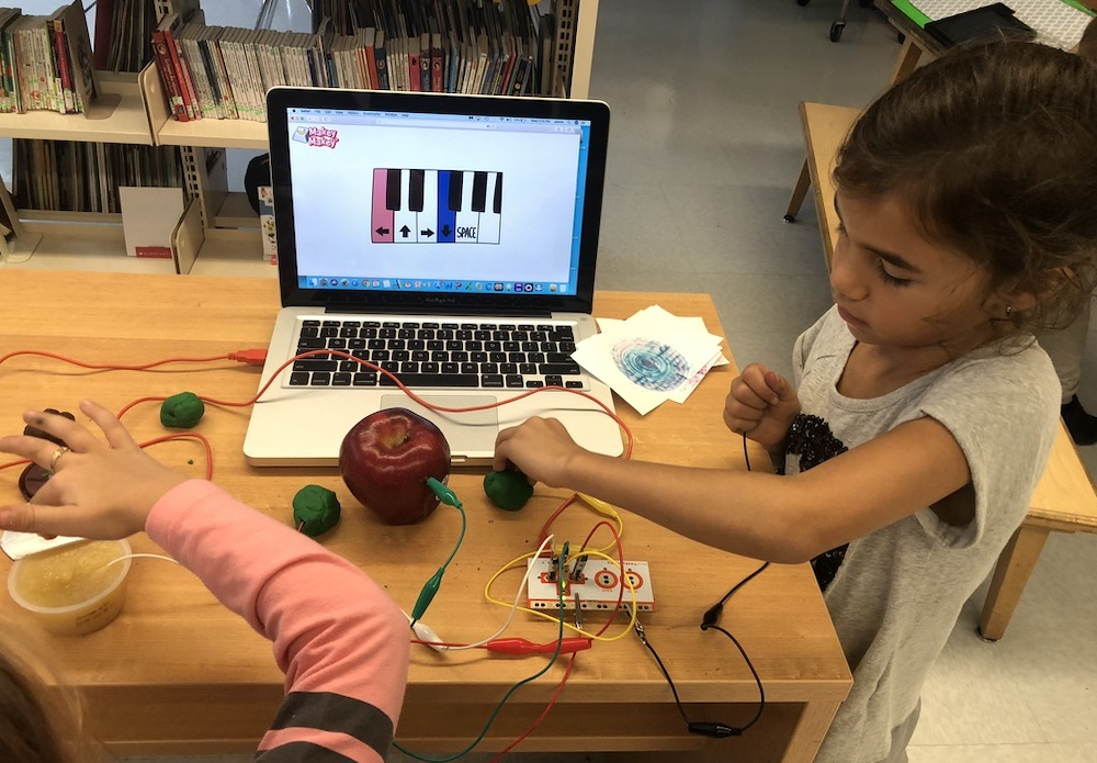 Two girls playing piano with Makey Makey